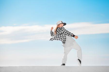Fashion child dancing over sky background. Foto de archivo