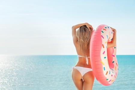 Summer Vacation. Enjoying suntan woman in white bikini with donut mattress near the swimming pool.