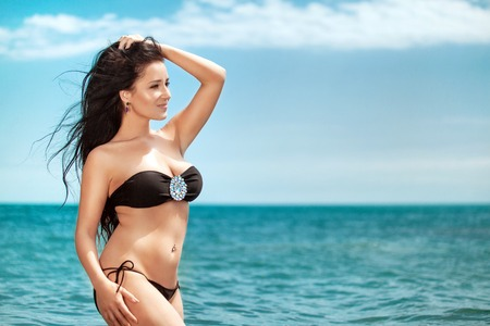 Overweight young woman in black swimsuit near the sea. Size plus or king size woman. Summer photo with copy space