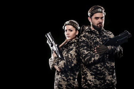 Heavily armed masked soldiers isolated on black background. Paint ball and laser tag sport games. Imagens - 82916156