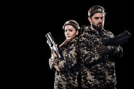 Zwaar bewapende gemaskerde die militairen op zwarte achtergrond worden geïsoleerd. Paintball en lasergamesportgames.