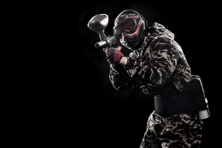 army face: Heavily armed masked soldier isolated on black background. Paint ball and laser tag sport games. Stock Photo