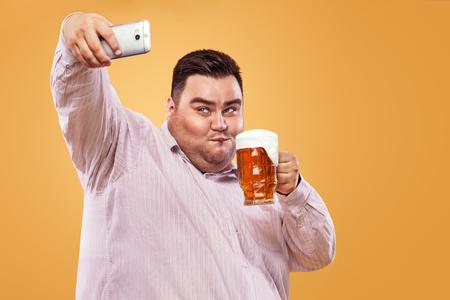 Joven gordo en oktoberfest con cerveza en fondo amarillo haciendo selfie foto en smartphone.