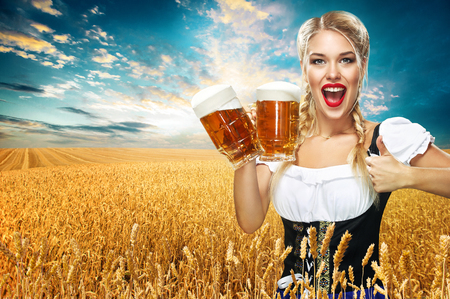 Half-length portrait of young sexy blonde with big breast wearing black dirndl with white blouse holding the beer mug Isolated on dark background Archivio Fotografico