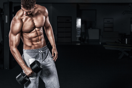 Athletic shirtless young sports man - fitness model holds the dumbbell in gym. Copy space fore your text. 写真素材