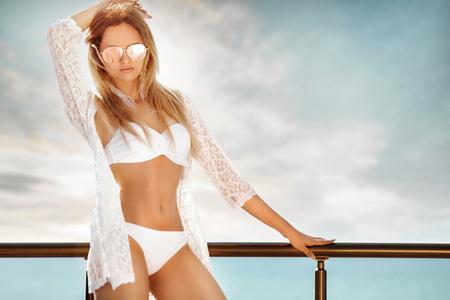 Het portret van vrouw in wit zwemt kostuum het stellen op het strand Stockfoto - 84717578