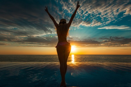 Summer Vacation. Silhouette of beauty dancing woman on sunset near the pool with ocean view. Stock Photo
