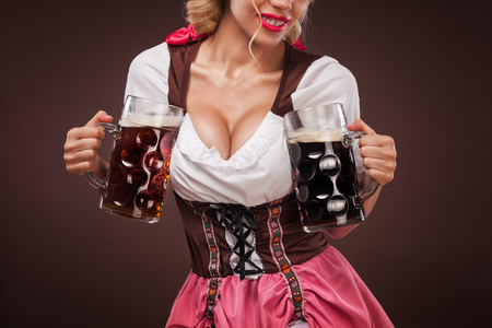 Closeup portrait of boyd Oktoberfest girl - waitress, wearing a traditional Bavarian dress, serving big beer mugs on black background.