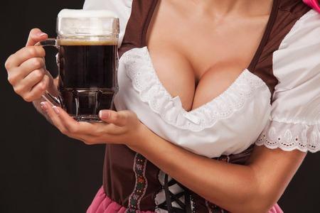 Closeup portrait de boyd Oktoberfest girl - serveuse, vêtue d'une robe traditionnelle bavaroise, servant de grandes tasses de bière sur fond noir. Banque d'images - 85188266