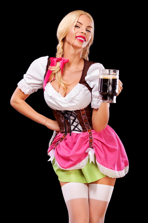 Portrait of Oktoberfest girl - waitress, wearing a traditional Bavarian dress, serving big beer mugs on black background. 스톡 콘텐츠