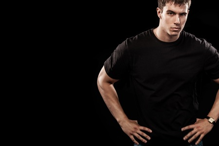 Portrait of fashionable handsome man in black t-shirt. Black background with copy space