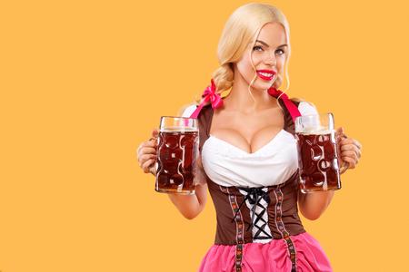 Junges sexy Oktoberfest-Mädchen - Kellnerin, ein traditionelles bayerisches Kleid tragend und dienen große Bierkrüge auf orange Hintergrund.