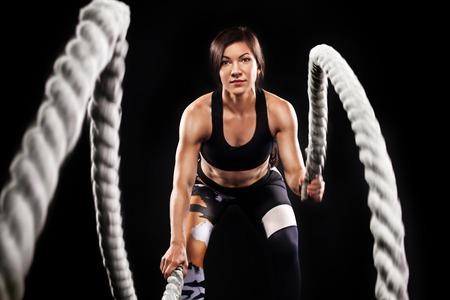 Battle touwen sessie. Aantrekkelijke jonge geschikte en gestemde sportvrouw die in functionele opleidingsgymnastiek uitwerken die crossfit oefening met springtouwen doen. Cross-fit workout-motivatie Stockfoto
