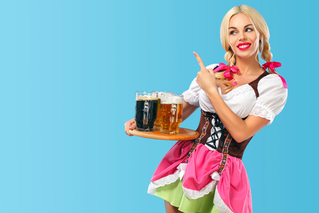 Young sexy Oktoberfest girl - waitress, wearing a traditional Bavarian dress, serving big beer mugs on blue background. Finger pointing on copy space