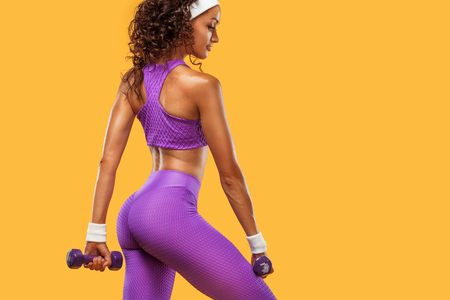 Sporty beautiful woman with dumbbells makes fitness exercising at white background to stay fit