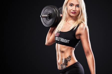 Sporty and fit beautiful woman with dumbbell exercising at black background to stay fit. Fitnwss workout motivation.