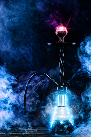 Hookah hot coals on bowl with black background. Stylish oriental shisha. Concept for bars and night clubs