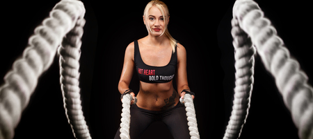 Battle ropes session. Attractive young fit and toned sportswoman working out in functional training gym doing crossfit exercise with battle ropes. Fitness and workout motivation