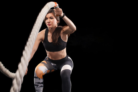 Battle ropes session. Attractive young fit and toned sportswoman working out in functional training gym doing exercise with battle ropes. Fitness and workout motivation