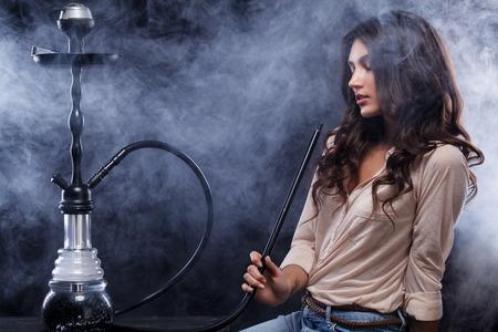 Young, beautiful woman in the night club or bar smoke a hookah or shisha. The pleasure of smoking. Sexy smoke.