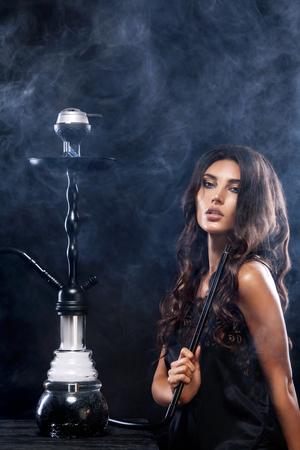 De jonge, mooie vrouw in de nachtclub of de bar rookt een waterpijp of een shisha. Het plezier van roken. Sexy rook.
