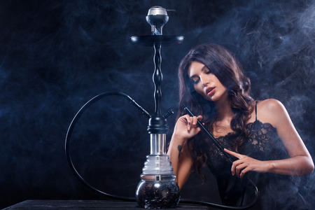 Young, beautiful woman in the night club or bar smoke a hookah or shisha. The pleasure of smoking. Sexy smoke. Imagens - 88366050