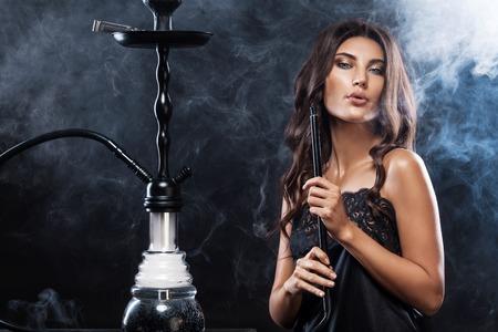 若い、夜のクラブやバーで美しい女性水ギセルやシーシャを煙します。煙ることの喜び。セクシーな煙。