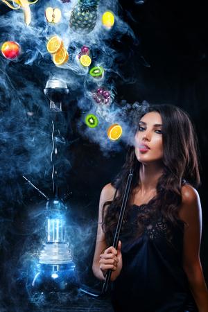 젊은, 아름다운 여자가 나이트 클럽, 바 물 담뱃대 또는 shisha. 흡연의 즐거움. 연기에 과일입니다. 공간을 복사합니다. 물 담 뱃 대 광고 개념입니다. 스톡 콘텐츠