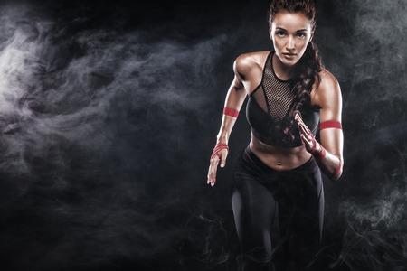 Un forte velocista atletico, donna, in esecuzione su sfondo nero che indossa la motivazione sportswear, fitness e sport. Concetto di corridore con spazio di copia.
