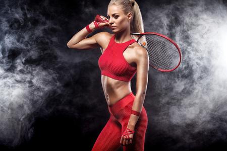 Schöner blonder Sportfrauentennisspieler mit Schläger im roten Kostüm