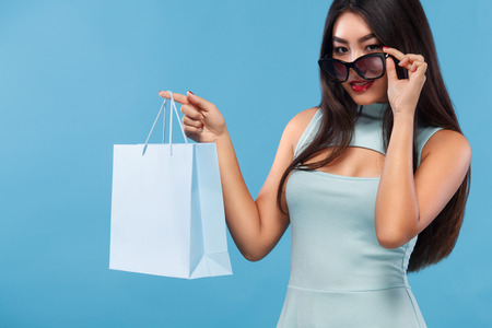 Happy asian woman at shopping holding bag and phone isolated on blue background on black friday holiday. Copy space for sale ads. Stock Photo