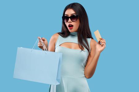 Glückliche asiatische Frau am Einkaufen, das Tasche und Telefon lokalisiert auf blauem Hintergrund an schwarzem Freitag-Feiertag hält. Platz für Verkaufsanzeigen kopieren Lizenzfreie Bilder