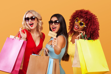 Double Eleven Shopping Festival . Three happy women in sunglasses after shopping. Afro american, asian and caucasian races. Black friday holiday. Concept for sale advertisement.
