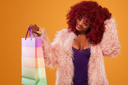 Afroe-amerikanisch Frau am Einkaufen, welches die rosa Tasche lokalisiert auf orange Hintergrund an schwarzem Freitag-Feiertag hält. Platz für Verkaufsanzeigen kopieren Double Eleven Einkaufsfestival.