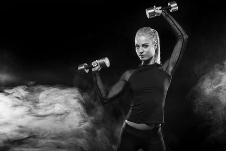 Sportliche Schönheit mit Dummköpfen macht die Eignung, die am schwarzen Hintergrund trainiert, um passend zu bleiben
