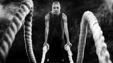 Kampf Seile Sitzung. Attraktiver Junge passte und tonte die Sportlerin, die in der funktionellen Trainingsturnhalle ausarbeitet, die Übung mit Kampfseilen tut. Fitness und Trainingsmotivation