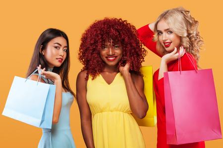 Drei glückliche Frauen. Afro amerikanische, asiatische und kaukasische Rennen. Einkaufen mit lokalisiert auf orange Hintergrund am schwarzen Freitag-Feiertag. Konzept für Verkaufsanzeige.