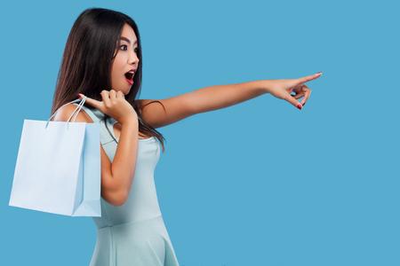 Überraschte asiatische Frau am Einkaufen, das Tasche und Punkte oben auf Kopienraum hält. Getrennt auf blauem Hintergrund am schwarzen Freitag-Feiertag.