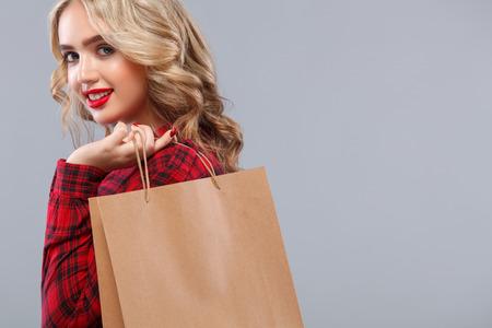 Blondine am Einkaufen, das Tasche lokalisiert auf grauem Hintergrund an schwarzem Freitag-Feiertag hält. Konzept für Verkaufsanzeigen. Lizenzfreie Bilder