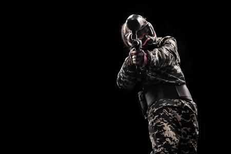 Schwer bewaffneter maskierter Soldat auf schwarzem Hintergrund isoliert. Paintball und Laserspiele.