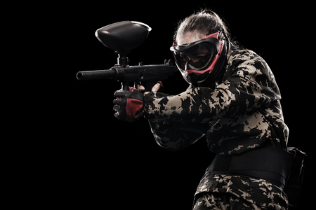 Heavily armed masked soldier isolated on black background. Paintball and lasertag sport games.