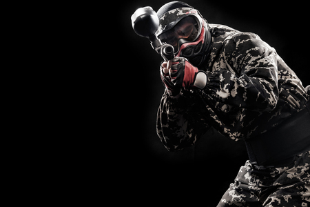 Heavily armed masked soldier isolated on black background. Paint ball and laser tag sport games. Stockfoto