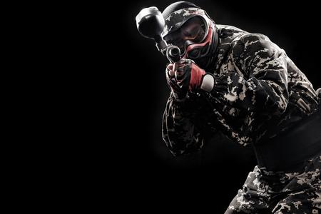Zwaar bewapende gemaskerde die militair op zwarte achtergrond wordt geïsoleerd. Paintball en lasergamesportgames.