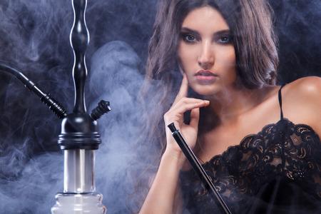 Young, beautiful woman in the night club or bar smoke a hookah or shisha. The pleasure of smoking. Sexy smoke. Imagens - 89755442