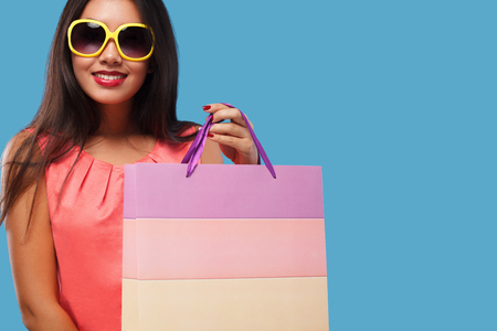 Happy asian woman at shopping holding bag and phone isolated on blue background on black friday holiday. Copy space for sale ads. Lizenzfreie Bilder