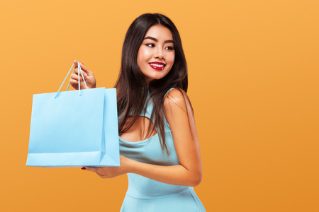Shopping Festival . Happy asian woman at shopping holding bag and phone isolated on blue background on Black Friday holiday. Copy space for sale ads.