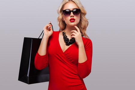 Blonde woman at shopping holding dark bag isolated on gray background on black friday holiday. Copy space for sale ads.