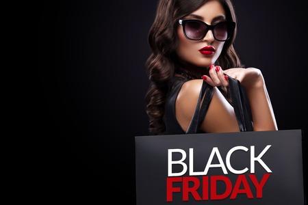 Shopping woman holding grey bag on dark background in black friday holiday Lizenzfreie Bilder