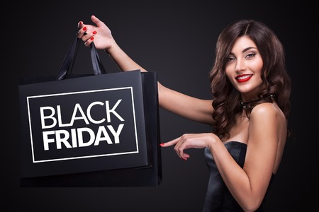 Sale. Young smiling woman showing shopping bag in black friday holiday.