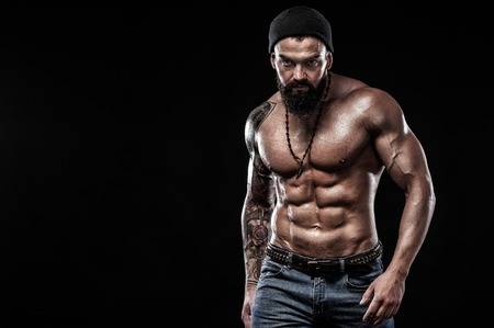 Handsome fit man posing wearing in jeans with tattoo. Sport and fashion concept isolated on black background. Stockfoto